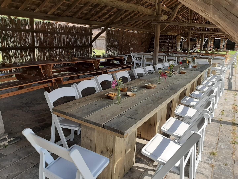 Huwelijksfeest met witte stijlvolle stoelen en steigerhouten tafels
